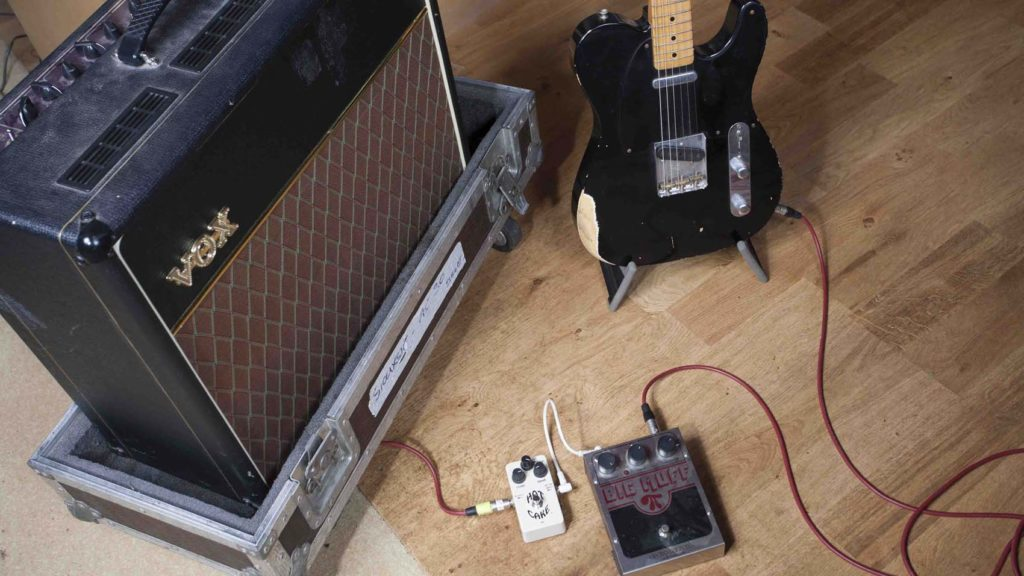 Fender guitar with Vox AC 30 amp and Big Muff pedal in a studio.